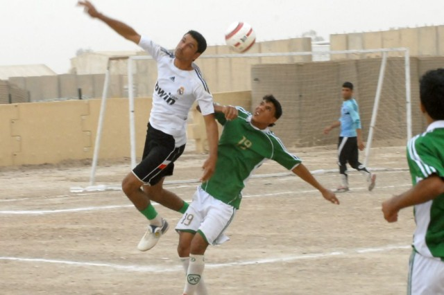 """A soldier assigned to the 33rd Iraqi Army Brigade (left) soars over a Babil University striker to """"head"""" the ball away from his goal during the championship game of the Armed Forces Day soccer tournament at Contingency Operating Site Kalsu, Iraq, May 15, 2010. Babil University eventually won the contest and claimed the tournament trophy in a ceremony that was attended by the Iraqi deputy governor of education and and the Iraqi Al Hurra news channel."""