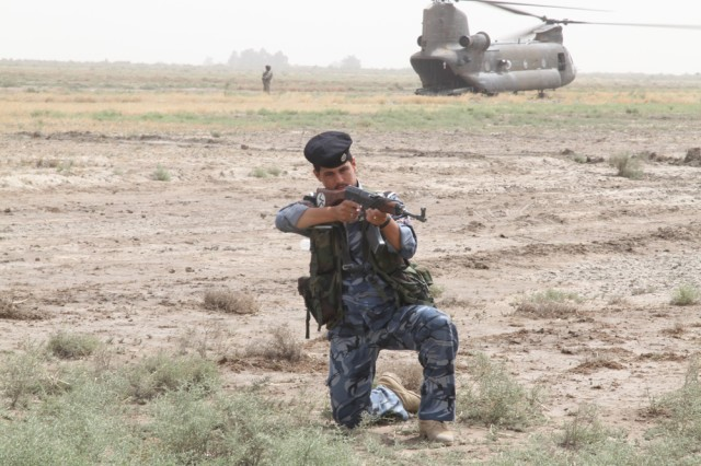 A Dhi Qar provincial police officer from the 6th Emergency Response Unit stands guard as part of a joint U.S. and Iraqi recovery operation for a UH-60 Black Hawk helicopter that was forced to land because of mechanical problem May 15, 2010. A quick reaction force from 3rd Platoon, Battery B, 3rd Battalion, 29th Field Artillery Regiment , 3rd Brigade Combat Team, 4th Infantry Division, flew in to provide security and assistance with recovery operations.  U.S. forces repaired the Black Hawk and flew it back to Contingency Operating Base Adder, Iraq, the next morning.   A CH-47 Chinook helicopter (shown in the background) flew-in Soldiers and supplies to assist with the recovery effort.