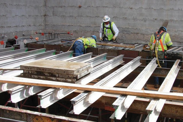 Workers place roof extension beams