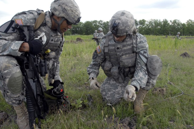 FORT HOOD, Texas - Spc. Aaron Butler (left) assists Lt. Col. Jack Vantress, 3rd Brigade Special Troops Battalion's commander, on tying a M-11 high strength blasting cap into a ring main during C Company, 3rd Brigade Combat Team Special Troops Battalion, 1st Cavalry Division's, demo range exercise at Fort Hood's Curry Demo Range, May 19.