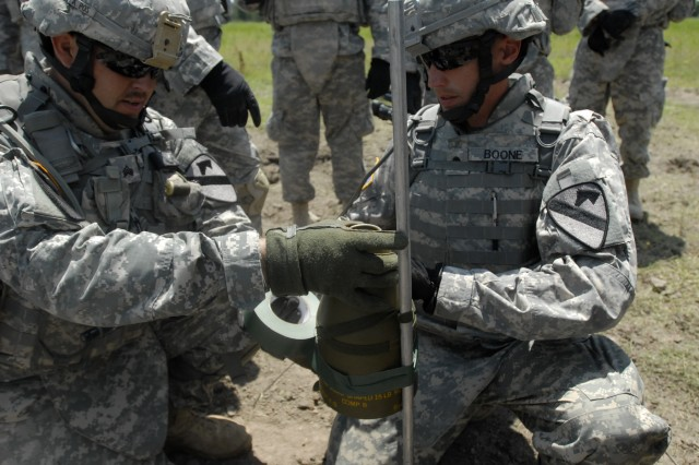 FORT HOOD, Texas - Sgt. Donald Clark (left) and Spc. Adam Boone use tape to attach a fifteen pounds shape charge to a pole, during C Company, 3rd Brigade Special Troops Battalion's , demolition range exercise, on Fort Hood, May 19. A shape charge is use to prepare a hole deep enough for a cratering charges.