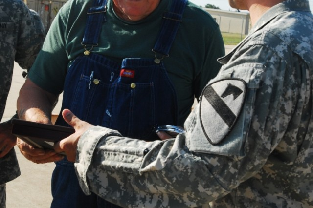 "FORT HOOD, Texas-Dean Scantling, a Glennwood, Ala. native, shakes hands with Col. John Peeler, the commander of 2nd Brigade Combat Team, 1st Cavalry Division, after being presented with two certificates, one making him an honorary member of the ""Black Jack"" brigade, and the other inducting him into the ""Order of the Spur,"" which allows him to wear the prestigious combat spurs, during a ceremony on Fort Hood, Texas, May 17."