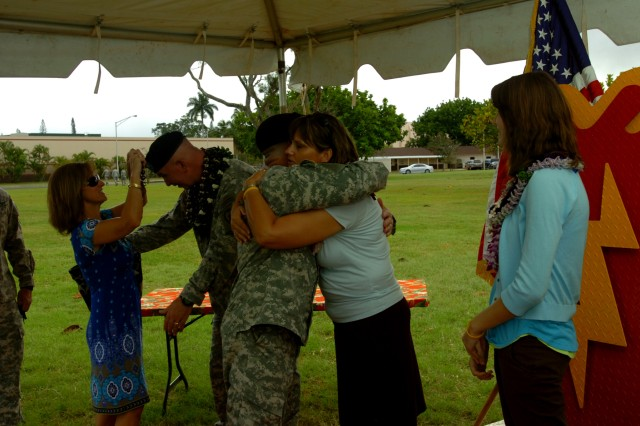 "SCHOFIELD BARRACKS, Hawaii -- The Nixon family (from left to right): Brig. Gen. James C. Nixon, the outgoing deputy commanding general - operations, 25th Infantry Division, Mrs. Debbie Nixon and Haley Nixon, are embraced and thanked by Soldiers and guests following  a ""Flying V"" ceremony at Sills, Field, here, May 25. The ceremony offered well-wishers the opportunity to bid Nixon farewell as he departs the division. Nixon planned and helped to execute the operations for three brigades in three provinces during the division's previous deployment to Iraq. (U.S. Army photo by Spc. Jesus J. Aranda, 25th Infantry Division Public Affairs Office)"