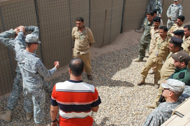 Sgt. Edward Ford and a Soldier from A Troop, 3rd Squadron, 1st Cavalry Regiment, 3rd Heavy Brigade Combat Team, 3rd Infantry Division, demonstrate search techniques during a reinforcement training class held at Contingency Operating Location Shocker, Iraq, in April, 2010. The students attending this class were members of the Iraqi Department of Border Enforcement.