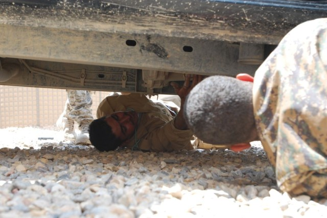 A pair of Iraqi Commandos inspect the undercarriage of a vehicle during reinforcement training at Contingency Operating Location Shocker, Iraq, in May, 2010.