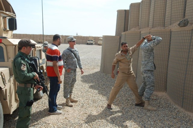 A pair of Iraqi Department of Border Enforcement agents demonstrate their personnel searching skills under the watchful eye off Sgt. Edward Ford, A Troop, 3rd Squadron, 1st Cavalry Regiment, 3rd Heavy Brigade Combat Team, 3rd Infantry Division, during joint training held at Contingency Operating Location Shocker, Iraq, in April, 2010.