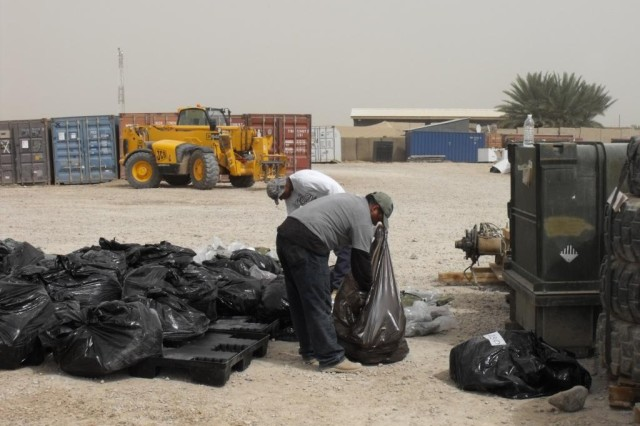Civilian employees of the 203rd Brigade Support Battalion, 3rd Heavy Brigade Combat Team, 3rd Infantry Division's material redistribution team sort supplies during a day's work at Contingency Operating Site Kalsu, Iraq.