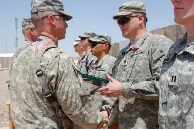 Col. Peter Jones, commander of the 3rd Heavy Brigade Combat Team, 3rd Infantry Division, hands a Bronze Star Medal certificate to Capt. Brandon Bergmann May 8, 2010, at Contingency Operating Site Kalsu, Iraq. Bergmann stands in line with 11 other members of the 30th Iraqi Army Brigade Military Transition Team, who all received the award for their support of the 3rd HBCT during Operation Iraqi Freedom.