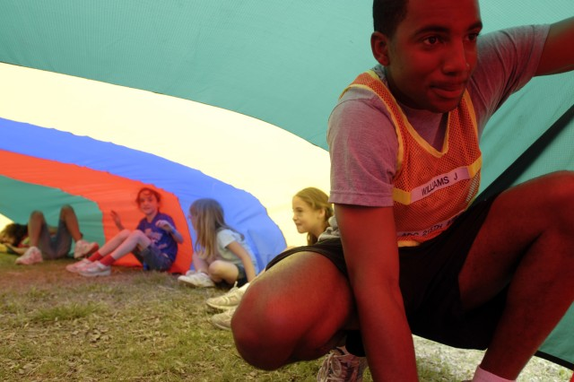 KILLEEN, Texas-Spc. Julius Williams, 215th Brigade Support Battalion, 3rd Brigade Combat Team, 1st Cavalry Division, traps air inside a parachute at Bellaire Elementary School, May 7, as part of a field day. Events like these connect the Soldiers of the unit with the students of the local school that they support in a fun, organized environment. Williams is a native of Spartanburg, S.C.