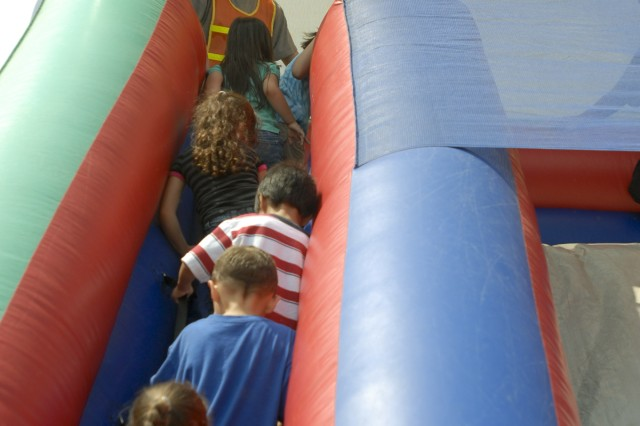 KILLEEN, Texas-Spc. Johnmichael Bruner, with 215th Brigade Support Battalion, 3rd Brigade Combat Team, 1st Cavalry Division, helps kindergarten students at Bellaire Elementary School to the top of an inflatable slide as part of a field day, May 7.