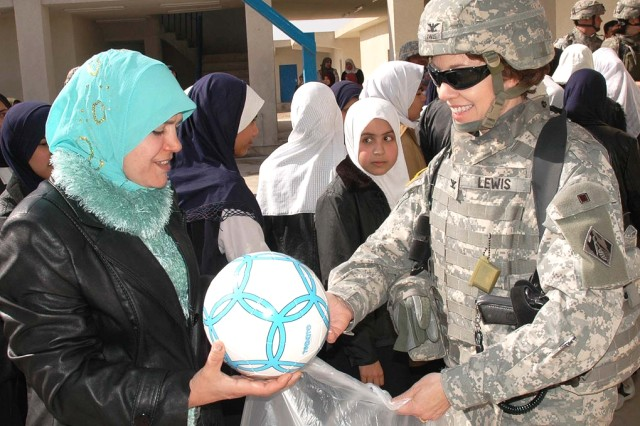 Col. Debra M. Lewis, as commander of Gulf Region Division's Central District, Army Corps of Engineers, presented soccer balls to the headmistress of a new girls high school in north Baghdad.