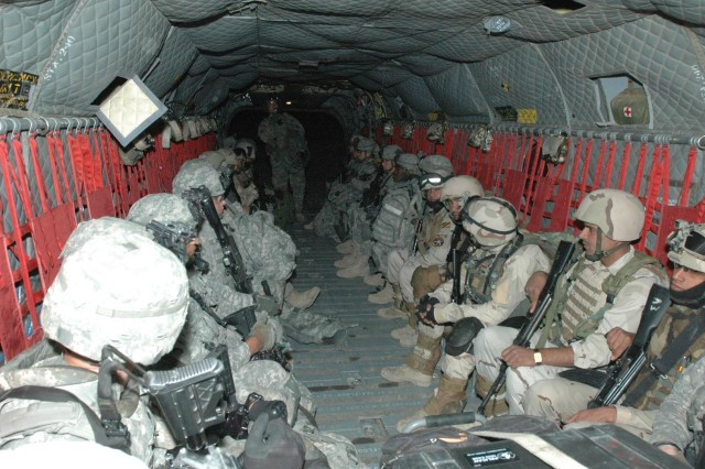 A crew chief (center) from Company B, 3rd Battalion, 25th General Support Aviation Battalion, Task Force Hammerhead, gives last minute instructions to a tripartite force of Iraqi Army, Iraqi Police and Peshmerga Soldiers, and their U.S. counterparts, prior to an air assault mission launching from Contingency Operating Location Cobra, in Salah ad- Din province, April 24.  (Photo by:  Sgt. 1st Class Tyrone C. Marshall, 25th Combat Aviation Brigade Public Affairs)