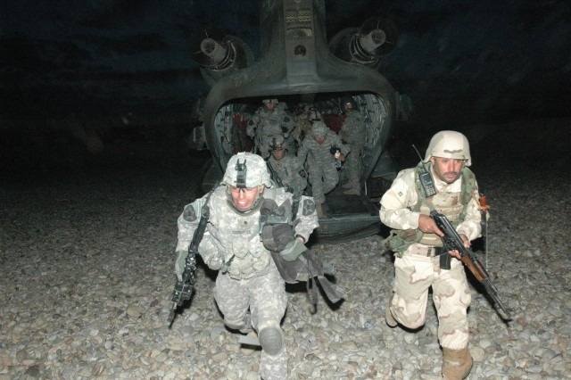 A tripartite force consisting of 4th Brigade, 1st Iraqi Army Division; Diyala Iraqi Police; and 3rd Peshmerga Brigade Soldiers, along with Soldiers from A Troop, 1st Squadron, 14th Cavalry Regiment, 3rd Stryker Brigade Combat Team, 2nd Infantry Division, rehearse hot-load training on a CH-47D Chinook helicopter at Contingency Operating Location Cobra, in Salah ad Din Province, April 24. The Chinook, piloted by a crew from 3rd Battalion, 25th General Support Aviation Battalion, Task Force Hammerhead, was part of an air assault for Operation Chelan III.   (Photo by Sgt. 1st Class Tyrone C. Marshall, 25th Combat Aviation Brigade Public Affairs)