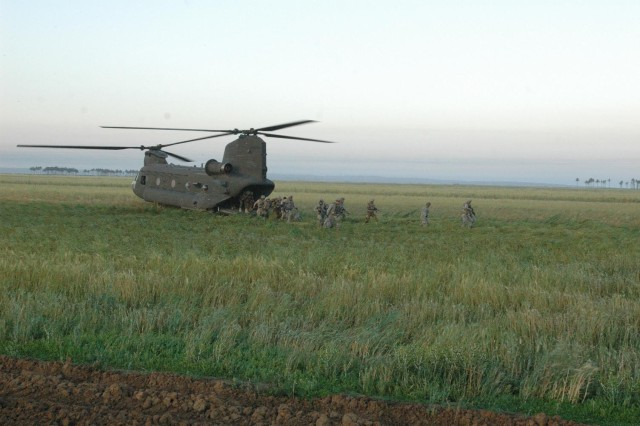 A tripartite force consisting of 4th Brigade, 1st Iraqi Army Division; Diyala Iraqi Police; and 3rd Peshmerga Brigade Soldiers, along with Soldiers from A Troop, 1st Squadron, 14th Cavalry Regiment, 3rd Stryker Brigade Combat Team, 2nd Infantry Division, are inserted by a CH-47D Chinook helicopter at a landing zone near the Lake Hamrin region of Salah ad-Din province during Operation Chelan III, April 24.   (Photo by Sgt. 1st Class Tyrone C. Marshall, 25th Combat Aviation Brigade Public Affairs)