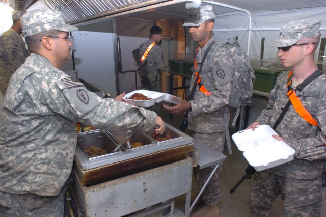 Specialist Stephen Villanueva (pictured left), food service specialist, Headquarters Support Company, 209th Aviation Support Battalion, Task Force Lobos, 25th Combat Aviation Brigade, serves Soldiers dinner at the 'Lobos Grill,' a remote TF Wings dining facility at Contingency Operating Base Speicher, near Tikrit, Iraq, March 18.   (Photo by: Staff Sgt. Mike Alberts  25th Combat Aviation Brigade Public Affairs)