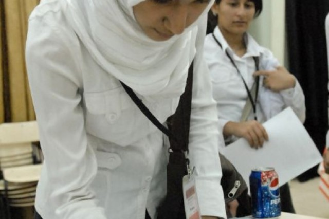 A student from the Hillah High School for Girls, in Hillah, Iraq, signs a photo that will be sent to U.S. students in Columbus, Ga.; following a video teleconference at Contingency Operating Site Kalsu, Iraq, May 5, 2010. Students from the girl's school and the Waeli High School for Boys used the internet to hold a discussion with students from Brookstone school and share about their cultures.