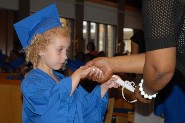 Cheyanne Norman, 4, receives her Strong Beginnings graduation diploma from lead teacher Debra Asberry Friday at the Main Post Chapel. Cheyanne was one of 40 preschoolers in the program.