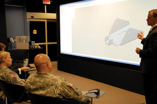 George Wolfe (far left) lead computer engineer, and Tim Knabel, mechanical engineer demonstrate the capabilities of the Advanced Visualization Room in the Depot Maintenance of the Future Facility during the recent Depot Assessment Visit.  The specific item being discussed is the antenna pull down bracket developed for Counter Radio Controlled Improvised Explosive Device Electronic Warfare.