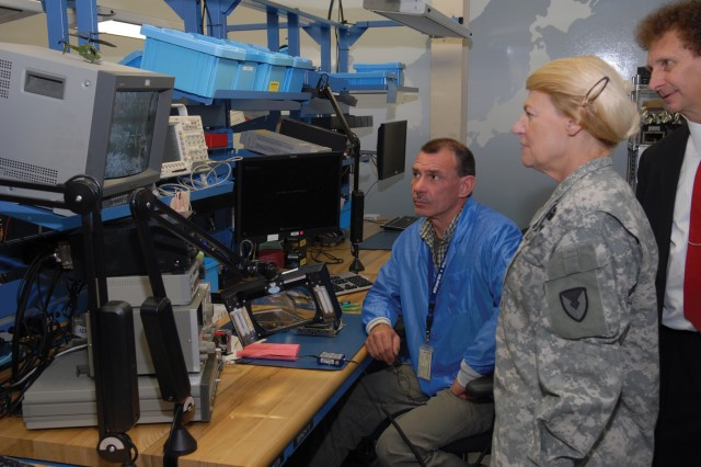 Al Kresge, electronics worker, shows Army Materiel Command Commander Gen. Ann E. Dunwoody a video using an AH-64 Video Recorder he just repaired in the Depot Maintenance of the Future Facility.
