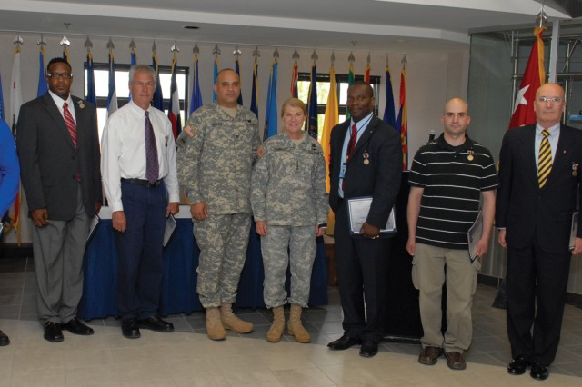 During her visit, AMC Commander Gen. Ann E. Dunwoody recognized personnel who have earned the Secretary of Defense Medal for the Global War on Terrorism.  From left, honorees Mark Bell, painting worker, Travis Curtis, AMCOM Liaison, Jerome  Demeck, Electrical Fabrication Support Branch chief, Col. Charles Gibson, depot commander, Dunwoody, Thomas Holmes, New Equipment Training Division chief, Anthony Volper, electronics worker, and Gail  Vonderheid, logistics management specialist.