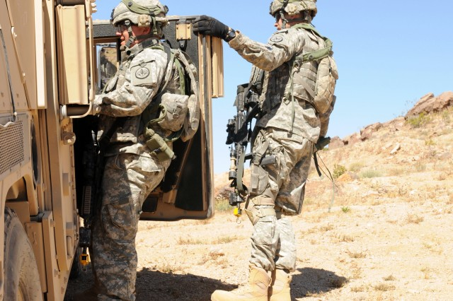 Second Lt. Kevin A. Garcia (right), a Colorado Springs, Colo., native, and an armor officer with Red Platoon, Dragon Company, 1st Squadron, 3rd Armored Cavalry Regiment, from Fort Hood, Texas, braves the steep hillside, strong winds and the weight of an up-armored door to hold the door open for 1st Lt. Ryan Divine (left), an Olathe, Kan., native, also an armor officer with 1-3 ACR, to use a radio to communicate with other elements of Dragon Co. during a live-fire exercise May 22 at the U.S. Army National Training Center Fort Irwin, Calif. (U.S. Army photo by Sgt. Jes L. Smith, 16th Mobile Public Affairs Detachment)