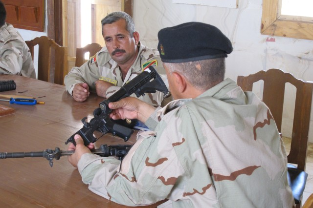Col. Muhammad Abd Al-Muhssan, of the 10th Field Factory Regiment, inspects an M4 Carbine during training conducted by the 64th Brigade Support Battalion, 3rd Brigade Combat Team, 4th Infantry Division, at Camp Mittica, Iraq, May 12, 2010.