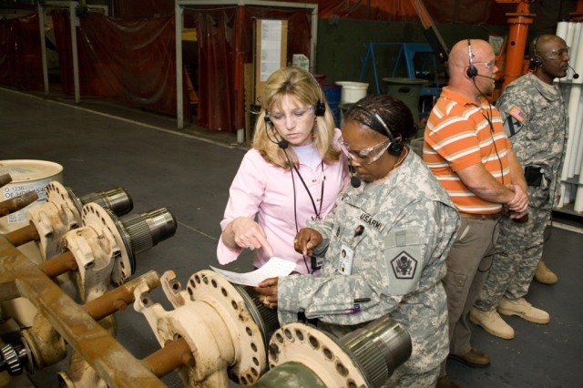 Sgt. Maj. Rozenia Carter and Anniston Army Depot's Kelly Clopton look over a routing tag in the Combat Vehicle Facility.