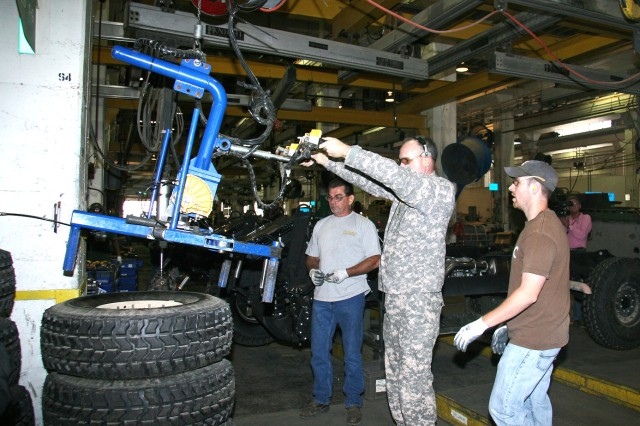 During his Red River Army Depot tour, Lt. Gen. James Pillsbury installs a tire onto the frame of a High Mobility Multipurpose Wheeled Vehicle (HMMWV). RRAD leaders escorting Pillsbury gave a round of applause once the job was complete. (U.S. Army Photo by Pam Barrett)