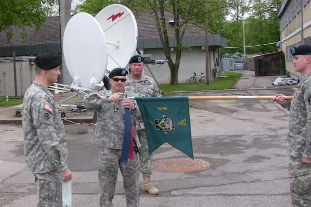 Lt. Col John D. Price places the physical fitness streamer onto Alpha DetachmentAca,!a,,cs guidon.