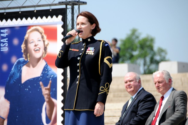 """Sgt. 1st Class Leigh Ann Hinton, a member of the United States Army Band, sings """"God Bless America,"""" May 27 in tribute to the song made famous by Kate Smith, now immortalized on a U.S. postage stamp, while Under Secretary of the Army Joseph W. Westphal, center, looks on."""
