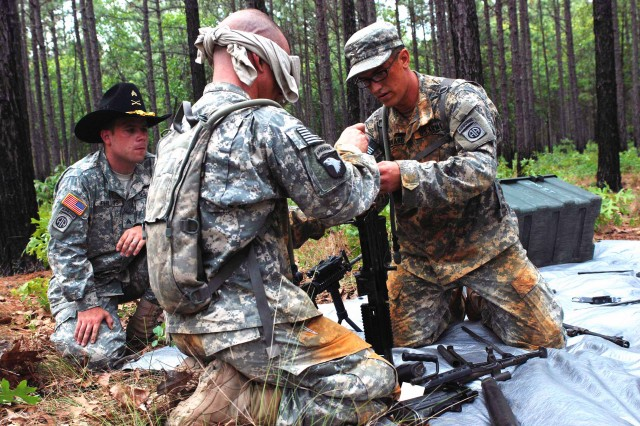 """Paratroopers with 1st Squadron, 73rd Cavalry Regiment, 2nd Brigade Combat Team, partnered up to assemble weapons at one station of the unit's Spur Ride May 12. Soldiers assisted their blindfolded teammates in putting together weapons by handing them pieces and talking them through the process while a """"Spur Holder,"""" left, supervised. The spur ride is an annual event that tests the motivation of each candidate and gives them the opportunity to earn spurs and Stetson hats of their own."""