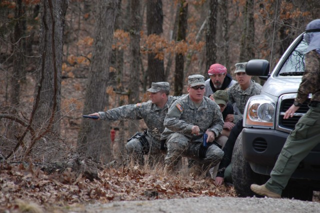 """Students in the Protective Services Training Course at the U.S. Army Military Police School, Fort Leonard Wood, Mo., protect their principals and interact with local """"Badistan"""" nationals during a training scenario."""