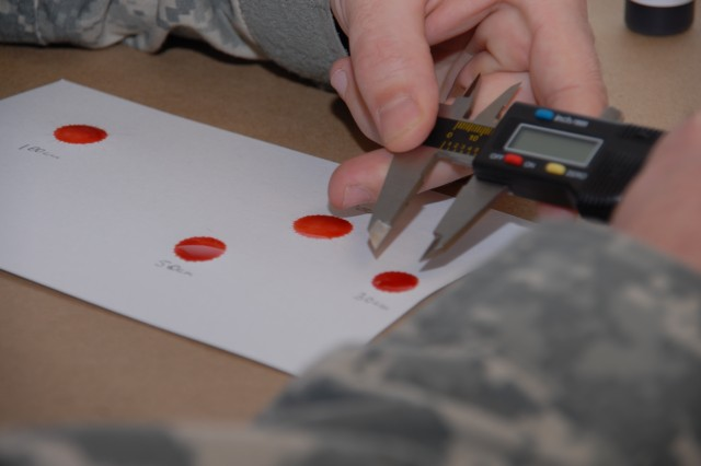 CID agents at a U.S. Army Military Police School advanced course at Fort Leonard Wood, Mo., measure blood splatter using synthetic blood.