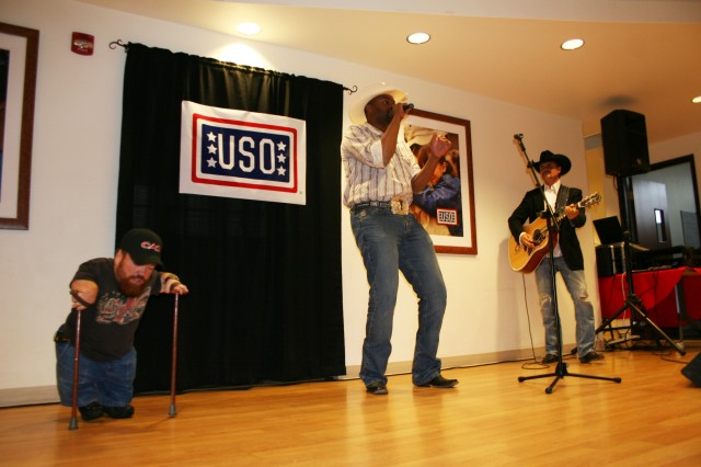 FORT CARSON, Colo.---Cowboy Troy, center, performs at the Fort Carson USO with Two Feet Fred, left, and John Rich. The trio entertained troops and their Families May 14.