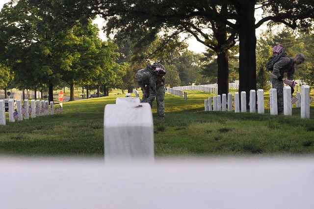 Soldiers assigned to Headquarters Company, 3rd U.S. Infantry Regiment (The Old Guard) place American flags in front of fallen veterans grave stones. Each year for the past 40 years, the 3rd U.S. Infantry has honored America's fallen heroes by placing American flags before the gravestones and niches of servicemembers buried at both Arlington National Cemetery and the U.S. Soldier's and Airmen's Home National Cemetery just prior to Memorial Day weekend.