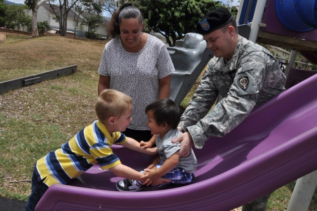 HONOLULU - Gavinn Bowling catches his foster brother Kanani Igawa after he goes down a slide at a playground in Red Hill Army housing. Supervising the fun is Army Sgt. Gregory Bowling, an information system administrator assigned to U.S. Pacific Command, and foster mother Regina Bowling.