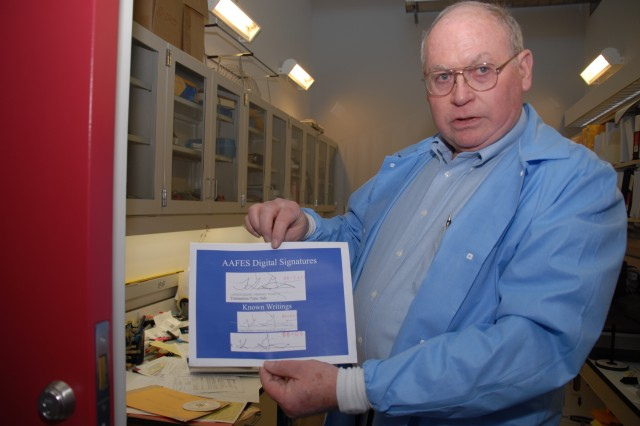 Jerry Gayle, a forensic document examiner, displays a comparison of a digital receipt signature against known writings.