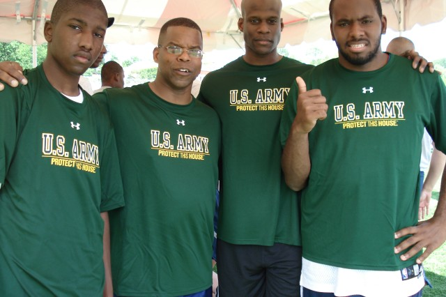 Sergeant Major Brian Jones  (second from left) and Capt. Marvin Morris (third from left) pose for a picture with two Special Olympic athletes. The Army team won a silver medal for the 4x100 relay race finishing in 2nd place at the District of Columbia Special Olympics on May 26, 2010.