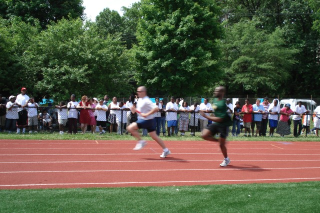 Capt. Marvin Morris (right) secures the Army team\'s second place finish during the 4x100 relay race at the District of Columbia Special Olympics on May 26, 2010.