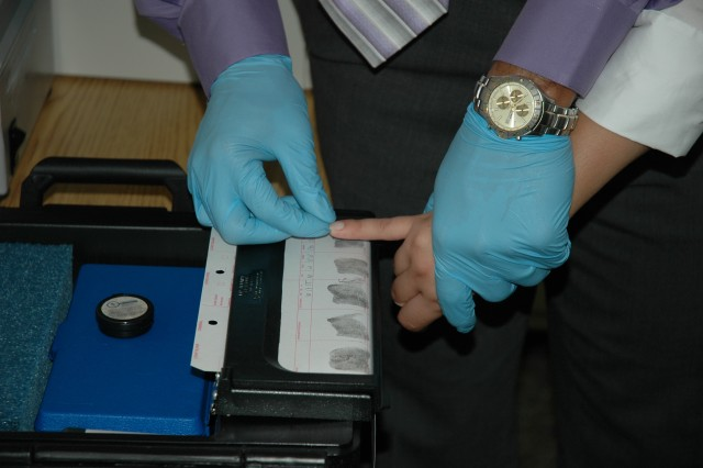 A subject is fingerprinted after being apprehended by CID special agents.