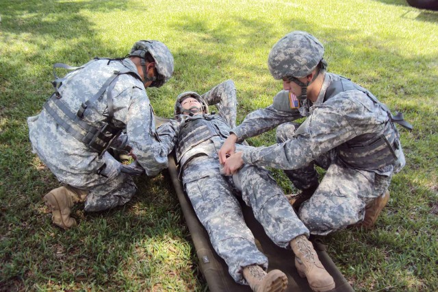 Sgt 1st Class Sergio Cortez,left, and Spc. Patrick Hartley, right, work to immobilize their patient, Spc. Lyndsey McConnell during the 7222nd Medical Support Unit's recent mass casualty exercise. Cortez, Hartley and McConnell all completed the Combat Lifesaver Course during the unit's weekend training.