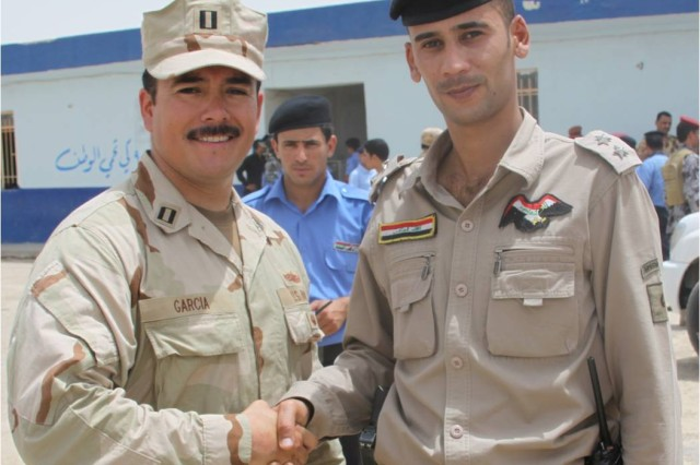 U.S. Navy Lt. Chris Garcia, commander of Detachment 1, Riverine Squadron (RIVRON) 1, deployed to Contingency Operating Site Garry Owen, Iraq, and 1st Lt. Hissinin, commander of a 50-man Special River Police Company, shake hands after the Iraqi unit's graduation ceremony in Amarah, May 15, 2010.
