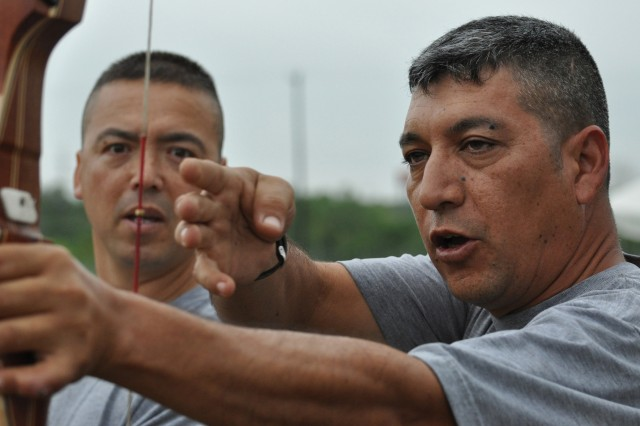 Staff Sgt. Raul Martinez (right) instructs Staff Sgt. Robert O'Hagan with the finer points of drawing a bow during a quarterly WTB adaptive sports competition at the FSH archery field, May 25.