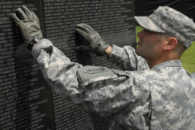 Officer Candidate Andrew Kennedy reaches for one of the 140 faux-granite panels May 25 during assembly of the Dignity Memorial Vietnam Wall at the National Infantry Museum.