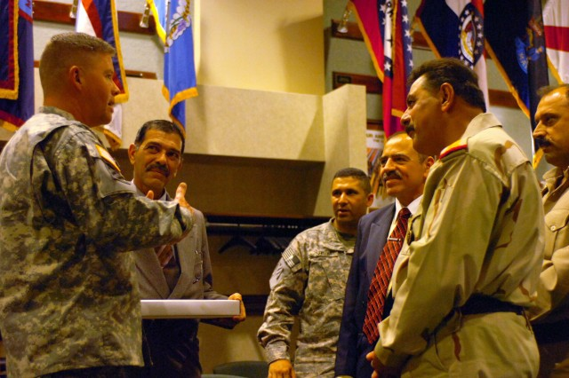 Fort Carson, Colo. - Maj. Gen. David G. Perkins, commander, 4th Infantry Division and Fort Carson, thanks staff Lt. Gen. Hasan Kareem Khudhair, right, commander, Ninewa Operations Center, for visiting the 4th Inf. Div. Afterward Perkins presented Khudhair with gift and told him that he looks forward to building a lasting bond with him when the division deploys.