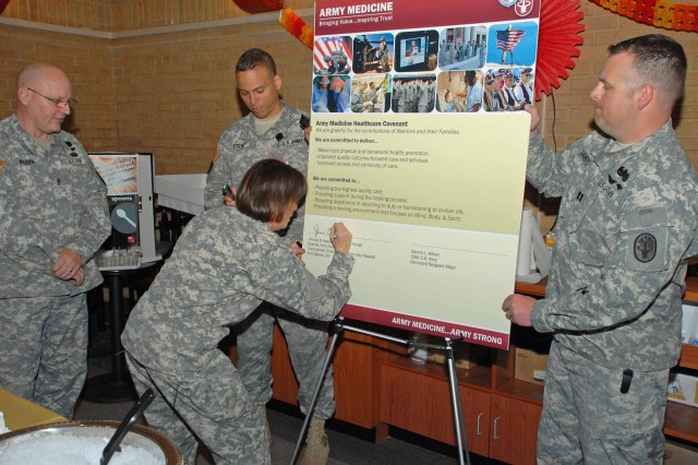FORT CARSON, Colo.--- Col. Jimmie Keenan, commander of Evans Army Community Hospital, signs the Army Medicine Healthcare Covenant document while, from the left, Command Sgt. Maj. Dennis Wilken, Sgt. Maj. Albert Crews and Capt. Chad Hamrick look on.