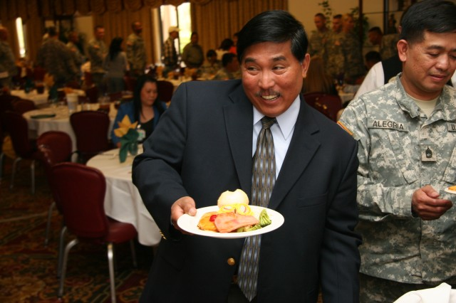 FORT CARSON, Colo.---Joey Bautista, Army Community Service, enjoys the food sampling at the Asian/Pacific Islander Heritage Celebration May 24. Bautista is of Filipino descent.