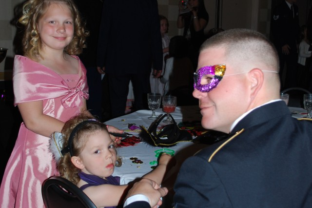 Princesses Emma and Haley Gladden enjoy a moment with the man behind the mask, Sgt. John Gladden, 25th Brigade Support Battalion, 1st Stryker Brigade Combat Team, 25th Infantry Division, Fort Wainwright, during the Armed Services YMCA fourth annual Father-Daughter Ball in Fairbanks, May 22. Soldiers, airmen, and other military men attended the gala with their daughters, bringing the evening's attendance to nearly 400. (Photo by Allen Shaw/Fort Wainwright PAO)