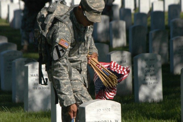 A Soldier from the 3rd U.S. Infantry Regiment known as the Old guard places flags on graves at Arlington National Cemetery in Arlington, Va., May 2009. (U.S. Army Photo)