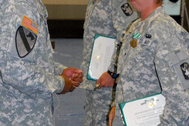 Col. Ron Kirklin, commander of the 4th Sustainment Brigade, 13th Sustainment Command (Expeditionary), awarded both Sgt. Michael Fox and Spc. Amber Burkhart with Army Commendation Medals for winning the Wrangler Brigade Soldier and NCO of the year competition at Fort Hood, Texas May 21. (U.S. Army photo by Pfc. Amy M. Lane)